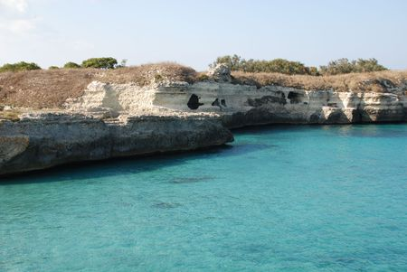 A beautiful stretch of rocky coastline with caves overlooking clear blue waters in Puglia, southern Italy.  The area is known by locals as The Poetry.  Stock Photo