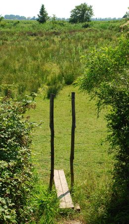 fenced: A small wooden stile in a field allows walkers to cross through a fenced off area