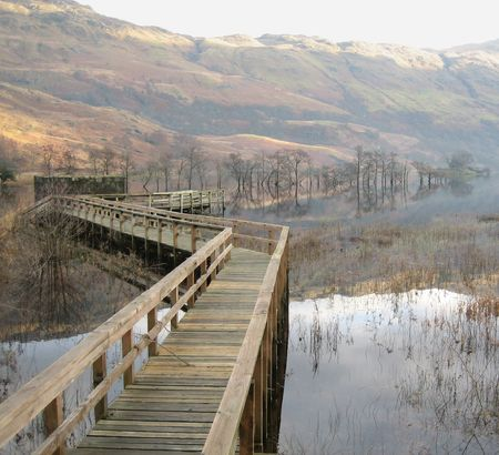 loch lomond: A walkway reaches out into the waters of Loch Lomond on a quiet Christmas Eve morning. There is a light mist obscuring the hills.  Stock Photo