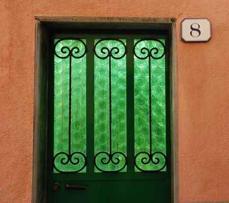 A Door With A Striking Green Glass Pane In It With Circular Patterns