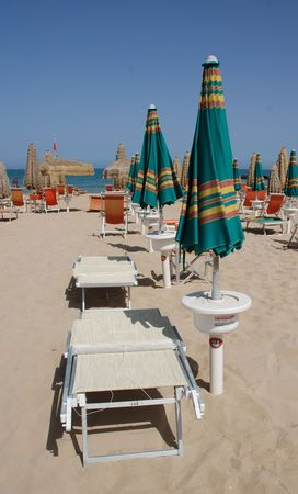 Green and orange beach umbrellas and deckchairs on a beach on a sunny summers day  photo
