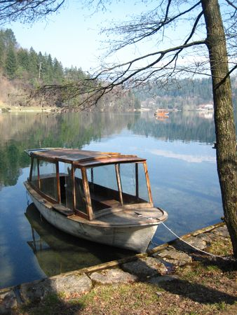 dappled: An old wooden row boat in dappled shade tied to the shore of Lake Bled, Slovenia