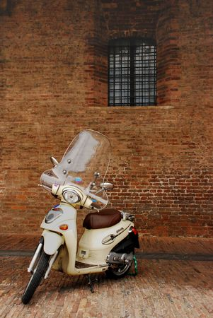 A white Italian moped is parked against a dark brick wall.  Stock Photo