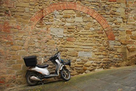 mopeds: A moped parked next to an old wall on a sloped street in Tuscany