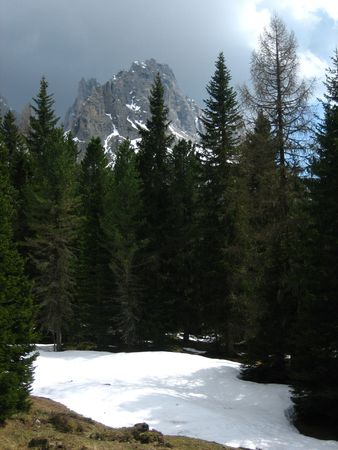 lake misurina: A snowy mountain near Lake Misurina in Northern Italy with foreground trees and a threatening grey sky  Stock Photo