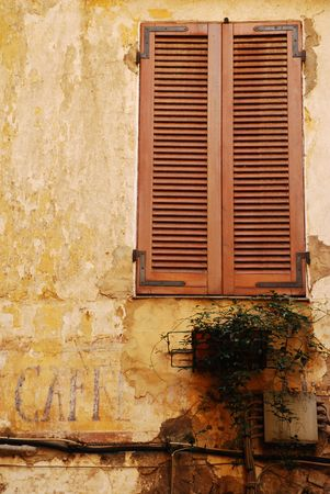 tatty: A newly painted window with shutters contrasts with the old cafe sign painted on the wall below it, Italy  Stock Photo