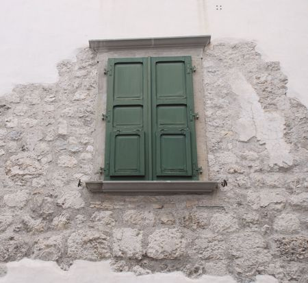 repaired: A green shuttered window in Venzone, Friuli. The wall is partially concreted and shows some of the original stonework  Stock Photo
