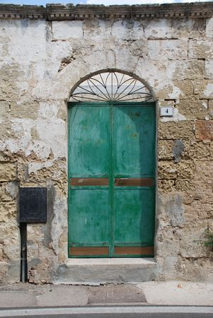 An old metal door in a building in the small southern Italian town of Acaya