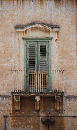 A green shuttered door on a balcony in Matera, southern Italy  Stock Photo