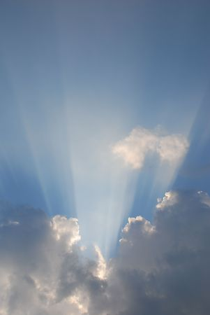 Strong sunbeams shine from behind a cloud in an otherwise clear blue sky