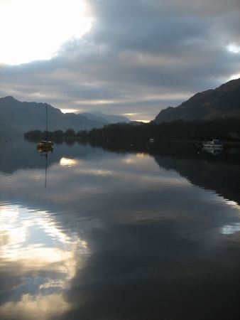 afloat: The waters of Loch Lomond relfect the clouds and mountains on a quiet Christmas Eve morning.   Stock Photo