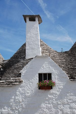 which: A traditional trullo house in Alberobello in Puglia, southern Italy. The trulli, which are protected under UNESCO World Heritage laws, are traditional limestone houses with domed or conical roofs, and are common in the Alberobello region