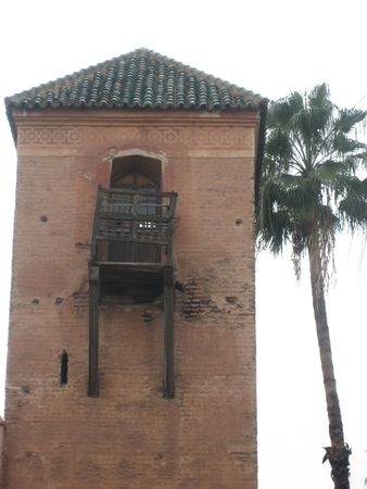 rickety: A tower in the central area of Marrakech with a tall palm tree next to it and a rickety old wooden balcony