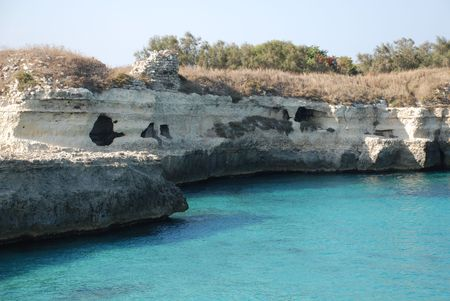 waters: A beautiful stretch of rocky coastline with caves overlooking clear blue waters in Puglia, southern Italy.  The area is known by locals as The Poetry.  Stock Photo