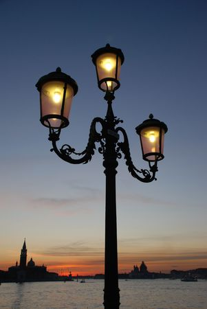 An old lampost is silhouetted against a sunset sky with Venice in the Background  Stock Photo