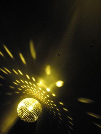 A disco ball shining under lights on a boats dance floor