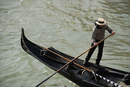 steers: A gondolier steers his gondola along a Venetian canal