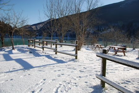 A lakeside picnic area in the snow  photo
