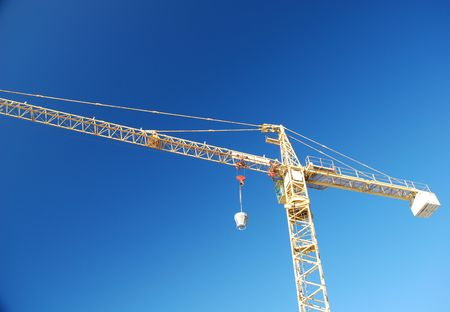 cloudless: A yellow crane against a clear blue sky  Stock Photo