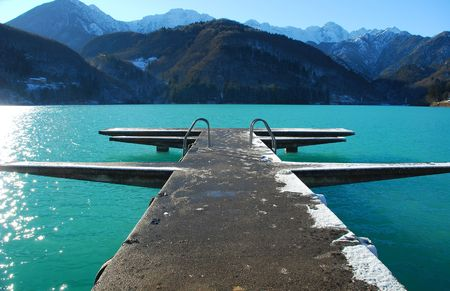 A diving platform juts out into the waters of Lagi di Barcis in north east Italy. It is mid-winter and no one is swimming  Stock Photo
