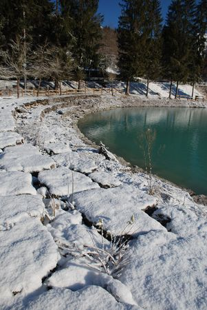 completely: The green waters of the north east Italian Lake Barcis, Lago di Barcis in Italian, in deepest mid-winter. The shore is composed of large stone blocks, now completely covered in snow