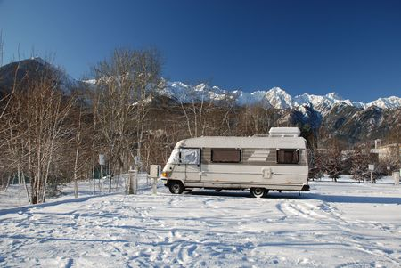 An A-Class  motorhome parked in an empty mountain car park in the snow