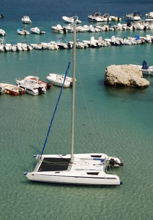 speedboats: A catamaran in a southern European harbour with a speedboats in the background