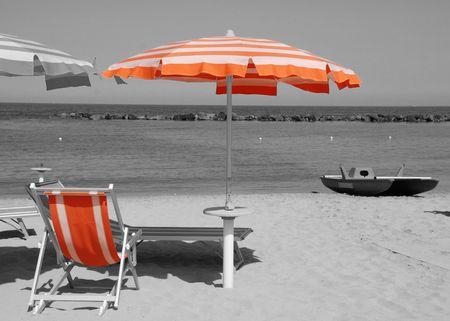 White and orange beach umbrellas and deckchairs on a black and white beach photo