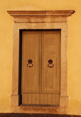 appears: The door of the historic Chiesa di San Giovanni church in the northern Italian village of Moimacco. The building is normally white, but here appears orange in the low golden sun of the early evening