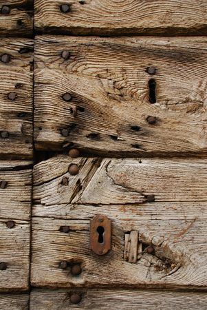 rusting: A close up shot of a rusted key hole in an old wooden door  Stock Photo