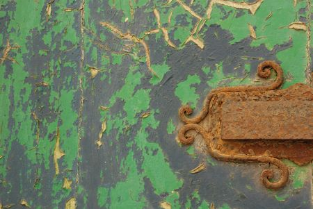A close-up shot of a door, with a rusted letterbox and peeling paint  photo