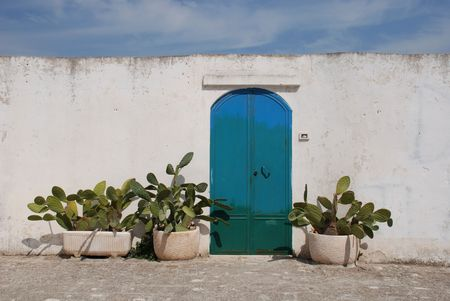 An old metal door in Ostuni (The White City) with cacti in planters beside it  Stock Photo