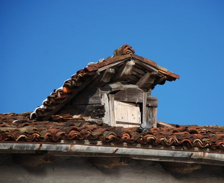 cloudless: An old red tiled roof with a small window in it  Stock Photo
