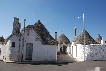 A street of trulli in Alberobello in Puglia, southern Italy. The trulli, which are protected under UNESCO World Heritage laws, are traditional limestone houses with domed or conical roofs, and are common in the Alberobello region  photo