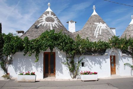 Trulli roofs in Alberobello, southern Italy - a UNESCO World Heritage site. On the roofs are two of the traditional symbols which are often painted on trulli roofs