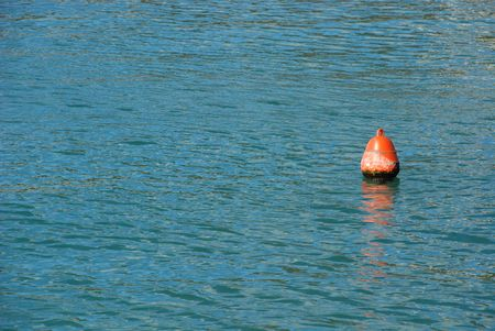 floats: A solitary red buoy floats in the open sea water