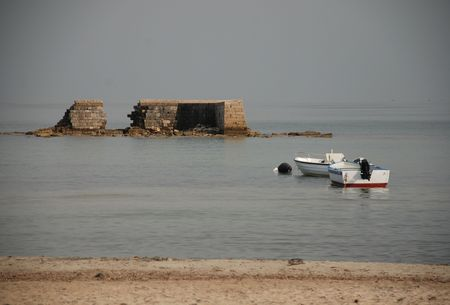 speedboats: A speed boat and rowing boat in the sea next to the crumbling sea wall at San Cataldo in southern Italy