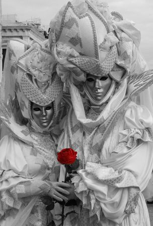 Two Venice carnival goers pose for photographs