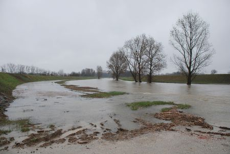 A normally dry river floods its banks after unusually heavy rains in north east Italy. In the foreground, the river is flowing over a small road bridge