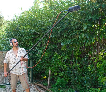 A sound engineer at work during on location recording bird sound in a hedge in Italy using a shotgun microphone with a wind protection shield