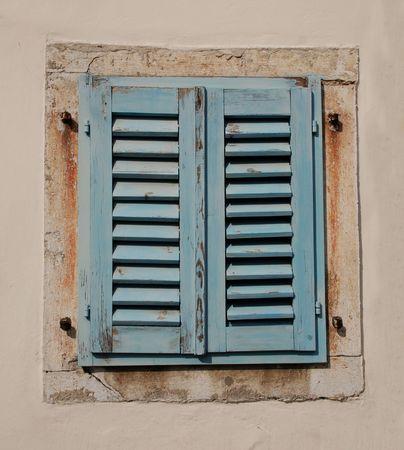 Blauwe houten shutters dekking van een venster in een oud gebouw in de Sloveense kust stad van Izola