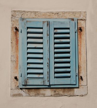 Blue wooden shutters cover a window in an old building in the Slovenian coastal town of Izola Stock Photo