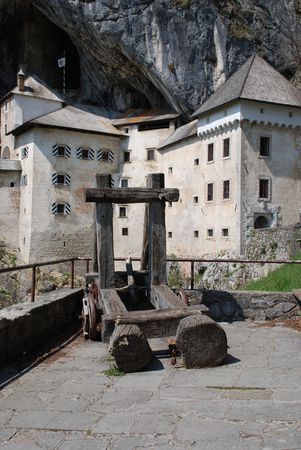 An old wooden catapult in front of the historic Predjama Grad castle in Slovenia which dates back to the twelfth century.  photo