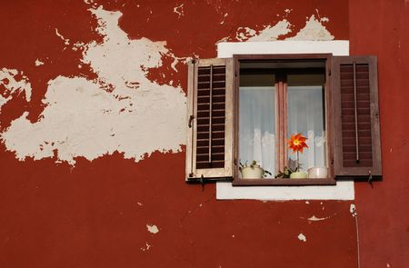 tatty: A window in the historic Slovenian coastal town of Izola with new brown shutters in a tatty red wall