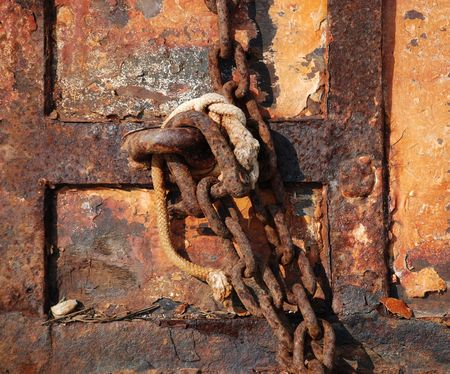 tatty: A close-up shot of an old rusted door, with an old rusted chain