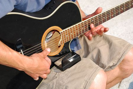 replaces: A musician tunes his acoustic guitar after replacing its strings