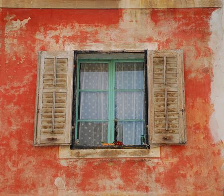 tatty: A window in the historic Slovenian coastal town of Izola with brown shutters in a tatty red wall Stock Photo