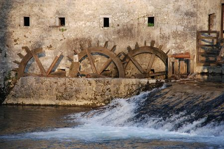 The water wheels of an old mill in Postojn in Slovenia in the dappled sunlight of late afternoon.. photo