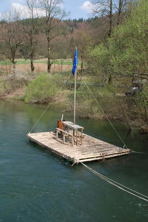 A small river raft on a river near the Slovenian town of Planina. There is a rusty oil drum on board, and the raft flies the European Union flag Stock Photo