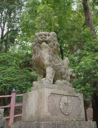 woodland sculpture: A lion statue or Shishi at Nara in Japan. In the background is a torii (shrine or temple gate) and a stone lantern  Stock Photo